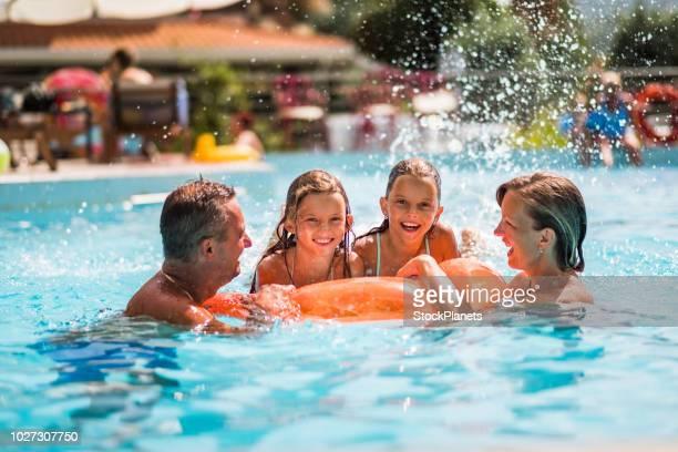 happy family enjoying in the pool - piscina pubblica all'aperto foto e immagini stock