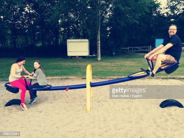 Happy Family Enjoying Seesaw At Playground