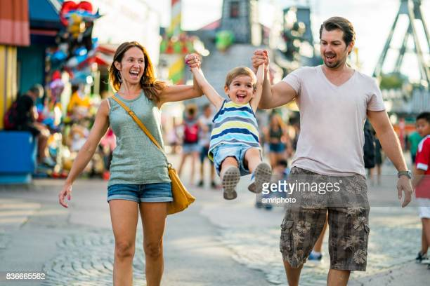happy family enjoying summer day in amusement park - traveling carnival stock pictures, royalty-free photos & images
