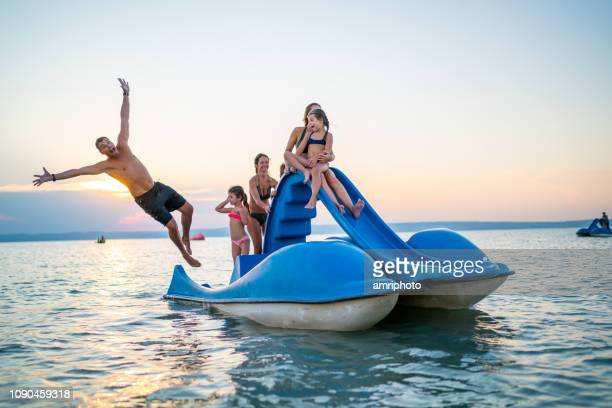 happy family enjoying summer sunset on lake with pedal boat - idiots stock pictures, royalty-free photos & images