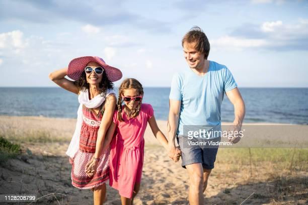 Happy family enjoying summer vacations on beach