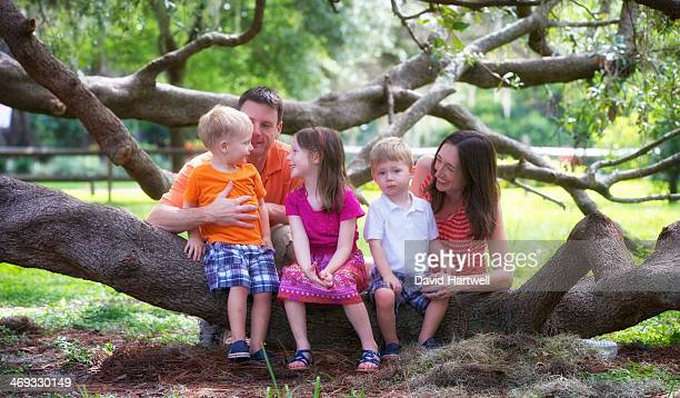 happy family enjoying the moment underneath a tree - girls in plaid skirts stock photos and pictures