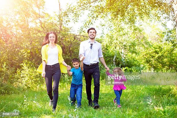 Glückliche Familie, die ihr Sommertag begehbarer Natur.