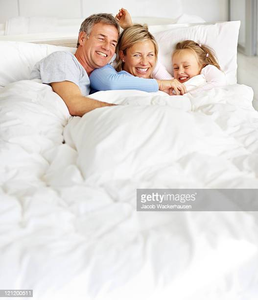 Happy family enjoying themselves on the bed