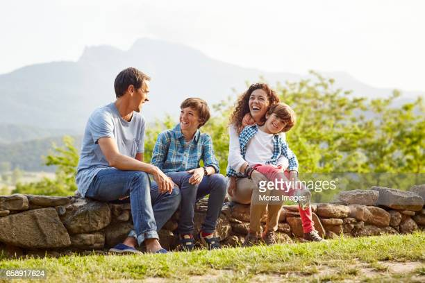 happy family enjoying while sitting on stone wall - stone wall stock pictures, royalty-free photos & images