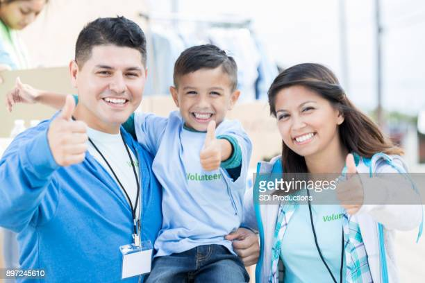 Happy family give a thumbs up during community charity event