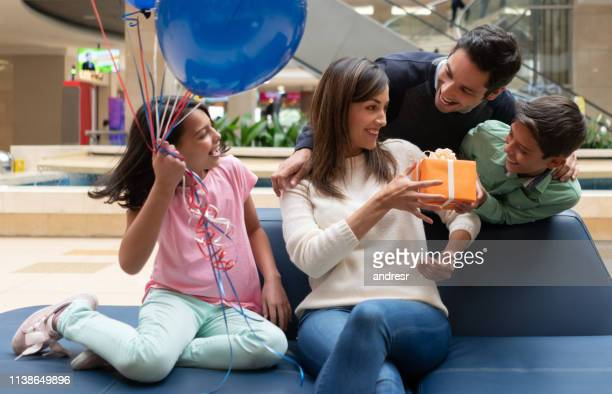 happy family giving a gift to her mother at the mall - womens day imagens e fotografias de stock