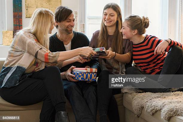 Happy family giving presents to daughter in living room