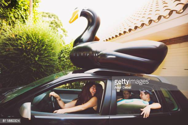 happy family going to the beach with huge black swan on the top of the car during travel vacations in the mediterranean sea. - cool cars stock pictures, royalty-free photos & images