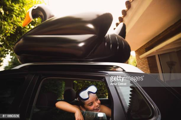 Happy family going to the beach with huge black swan on the top of the car during travel vacations in the Mediterranean sea.