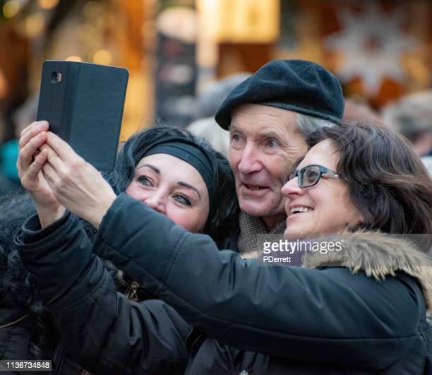 ハッピーファミリーグループは、プラハのクリスマスマーケットで selfie を取ります。