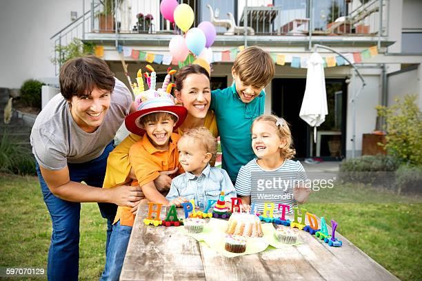 Happy family having a childrens birthday party in garden