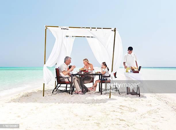Happy family having a dinner at the beach