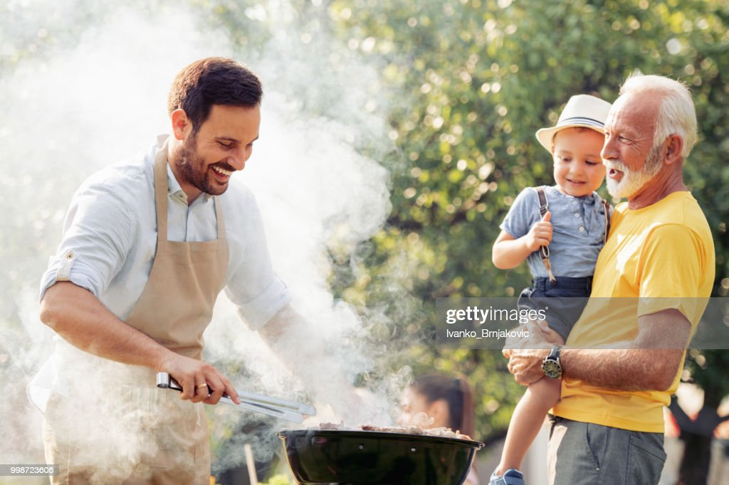 Happy family having barbecue party at summer garden : Stock Photo