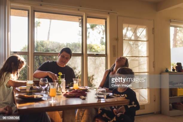 happy family having breakfast at dining table - frühstück stock-fotos und bilder