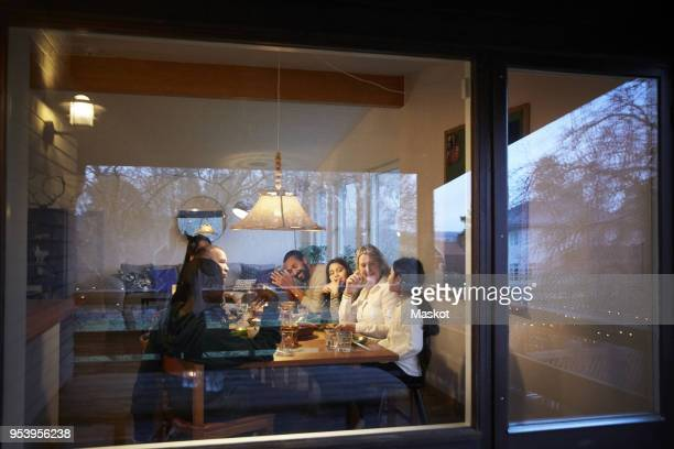 Happy family having dinner at table seen through glass window during sunset