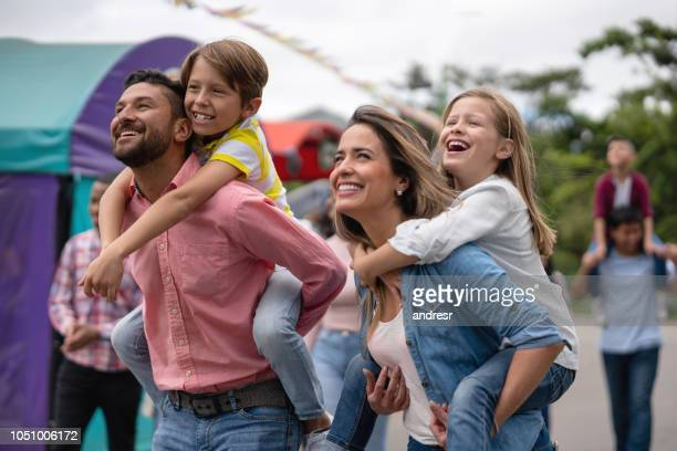 happy family having fun at an amusement park - traveling carnival stock pictures, royalty-free photos & images