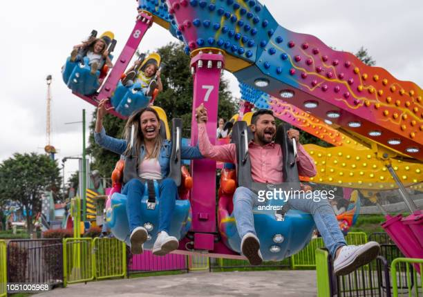 happy family having fun in an amusement park - amusement park ride stock pictures, royalty-free photos & images