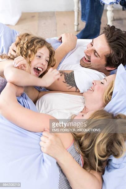 happy family having fun in bed