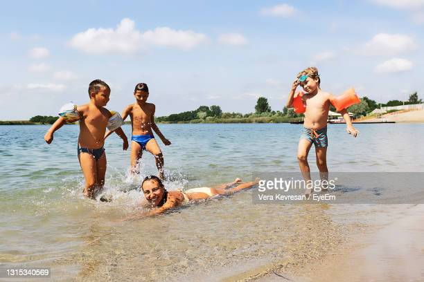 happy family having fun in the water at the beach during summer holiday. - sea swimming stock pictures, royalty-free photos & images
