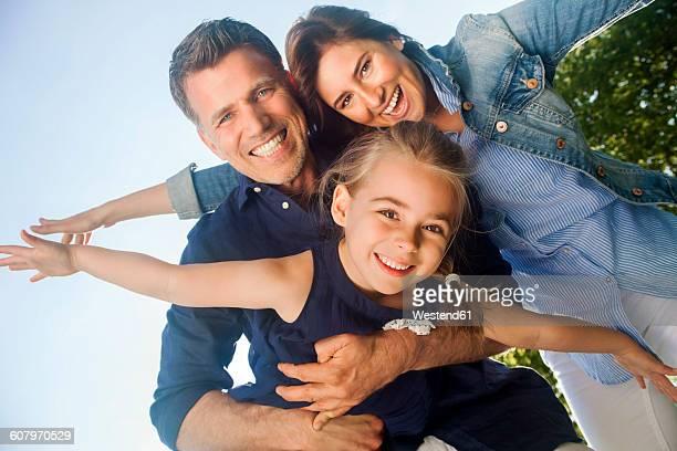 Happy family having fun, pretending to fly