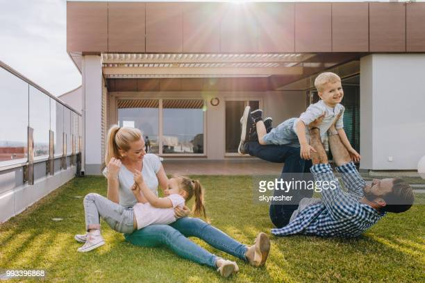 happy family having fun while playing on grass in front of their penthouse. - penthouse girls stock pictures, royalty-free photos & images