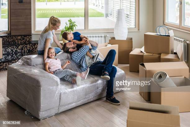 happy family having fun while taking a break from relocating into new apartment. - unpacking stock pictures, royalty-free photos & images