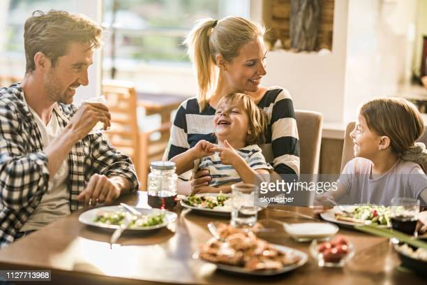happy family having fun while talking during lunch time at dining table. - family stock pictures, royalty-free photos & images