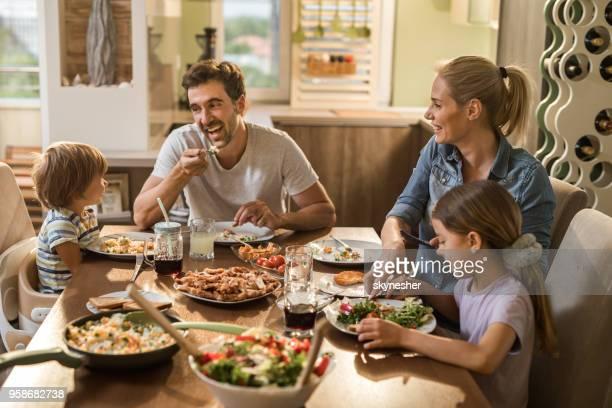 Família feliz se divertindo enquanto falava durante a hora do almoço na sala de jantar.