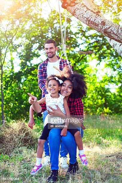 happy family having fun with a swing in the forest - vertical stock pictures, royalty-free photos & images