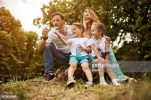 Happy family having fun with bubble wand in nature.