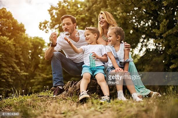 happy family having fun with bubble wand in nature. - familie mit zwei kindern stock-fotos und bilder