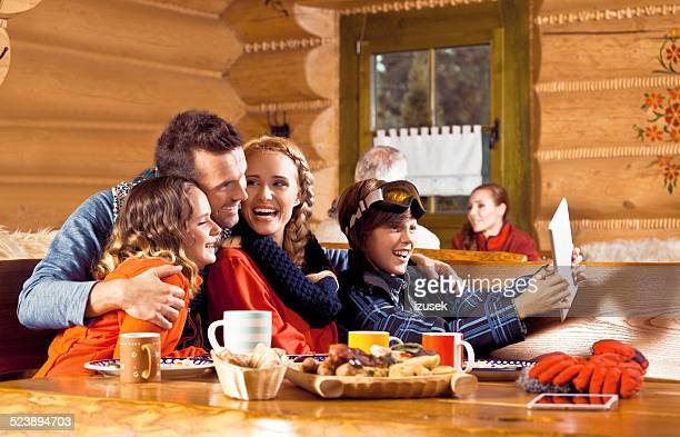 Happy family having lunch after skiing, taking selfie