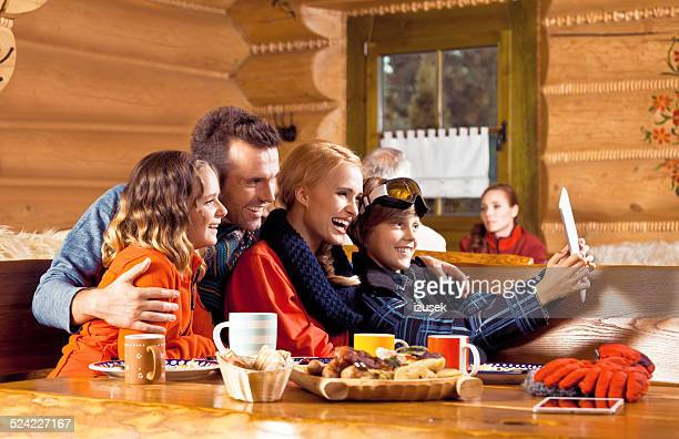 Happy family having lunch after skiing, using digital tablet
