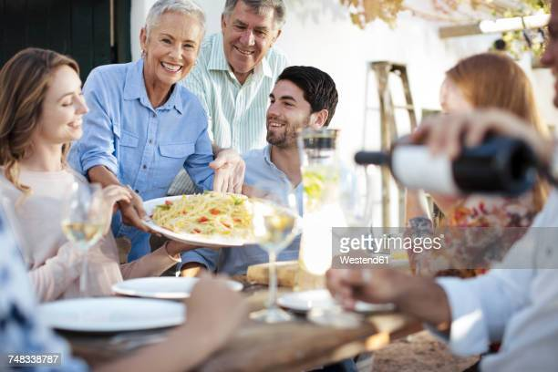 happy family having lunch together outside - groupe moyen de personnes photos et images de collection