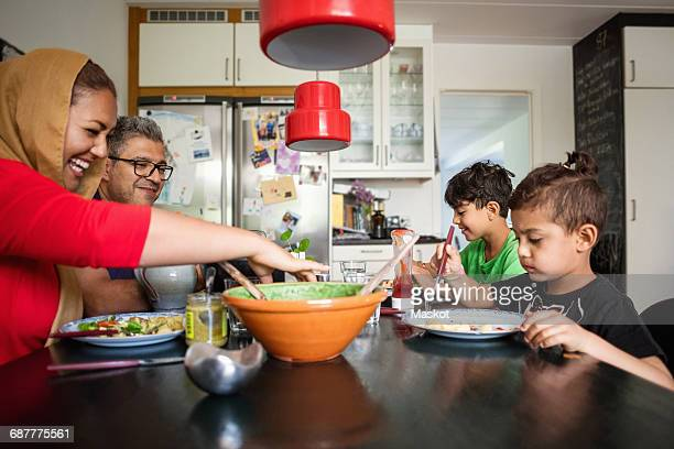 happy family having meal at dining table - family with two children stock photos and pictures