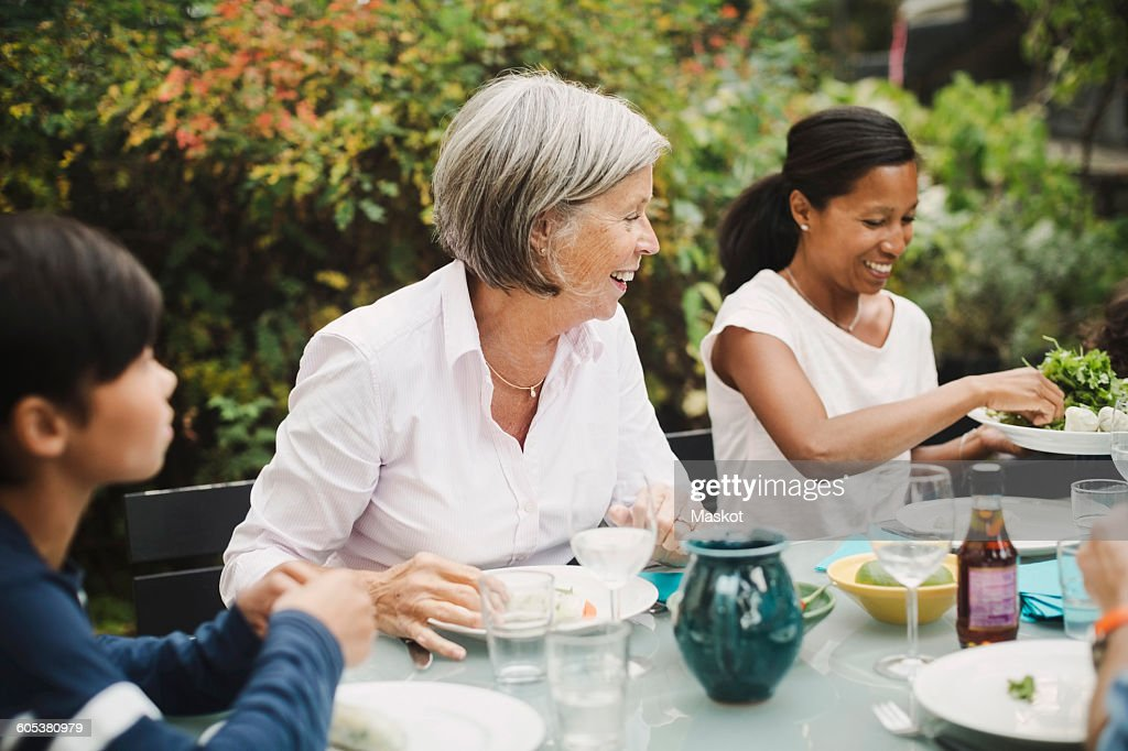 Happy family having meal at table in yard : Stock Photo