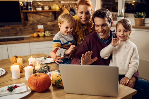 Happy family having video call before Thanksgiving meal at home. 1282791442