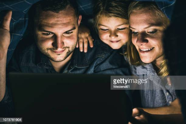 happy family hiding under blanket, watching film on laptop - wonder 2017 film stock pictures, royalty-free photos & images