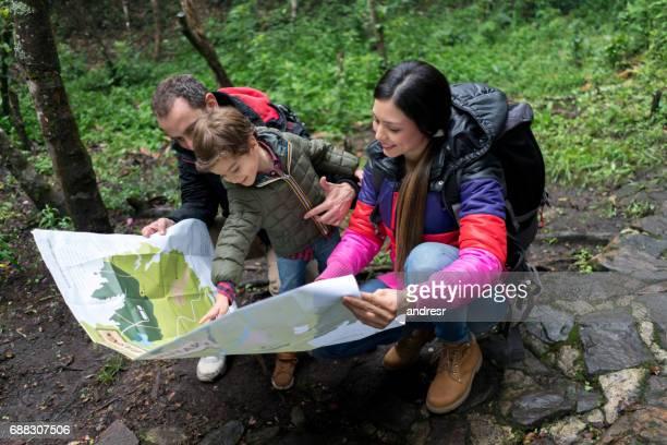 Senderismo familiar feliz y mirando un mapa