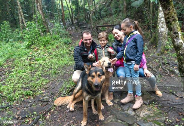 Happy Family Hiking Outdoors With Dogs