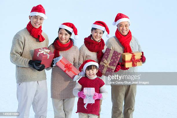 Happy family holding Christmas gifts