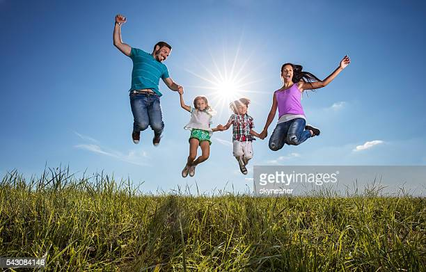 Happy family holding hands and jumping against the sky.