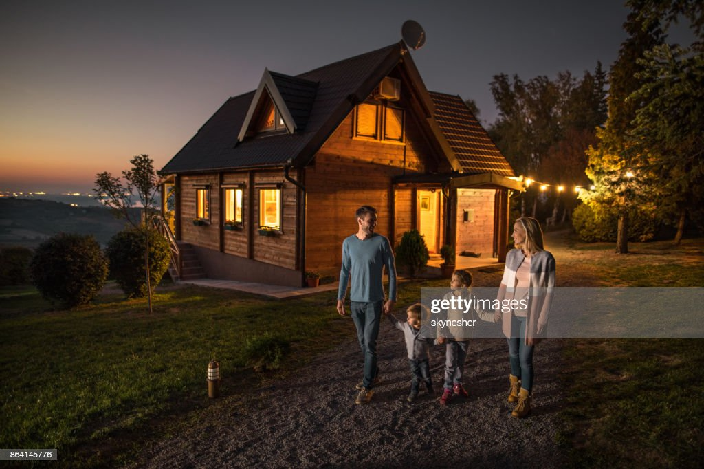 Happy family holding hands and walking by their chalet in the evening. : Stock Photo