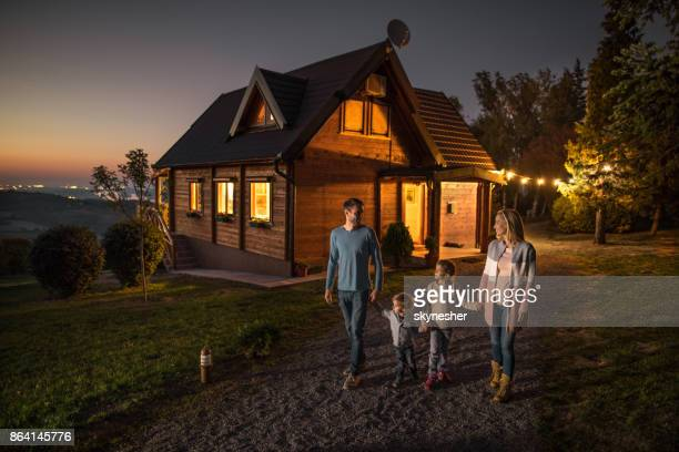 Happy family holding hands and walking by their chalet in the evening.