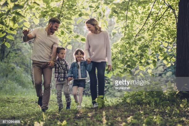 glückliche familie hand in hand und zu fuß durch den wald. - familie mit zwei kindern stock-fotos und bilder