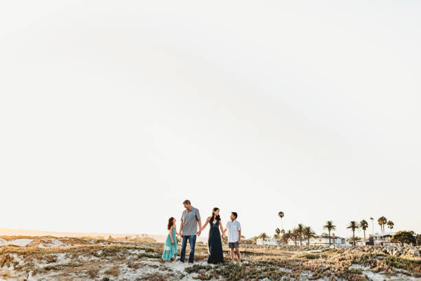 Happy family holding hands standing on beach
