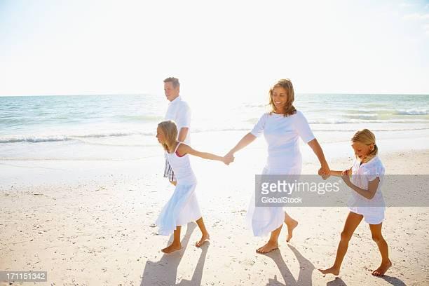 幸せな家族の手を歩きながら、ビーチの上