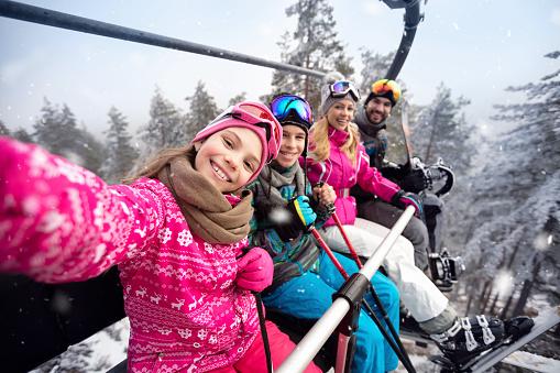 Happy family in cable car climb to ski terrain 909203164