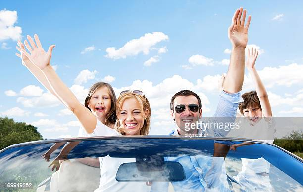 Happy family in convertible car.